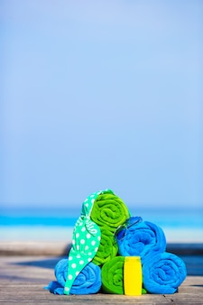 Beach and summer vacation accessories concept - close-up of colorful towels, swimming goggles and sunblock