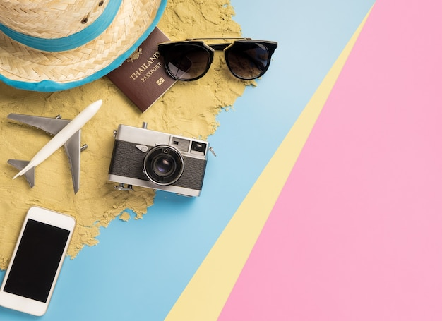 Beach summer vacation travel accessories and fashion on sand and blue yellow pink pastel background