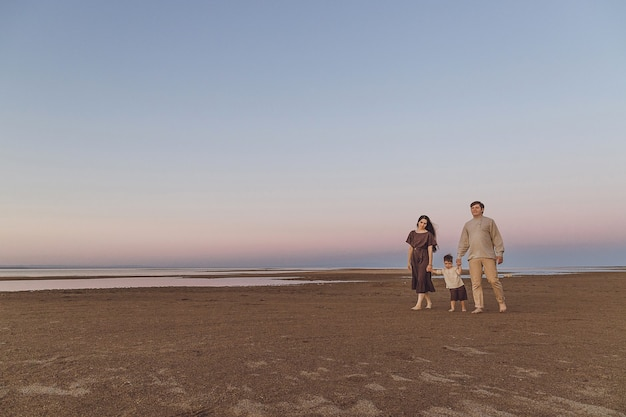 Beach sunrise with family and dog walking down the beach. family look linen clothes. copy space.
