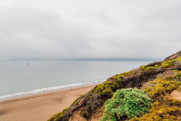 岩に囲まれたビーチと曇り空の下、霧に覆われた海