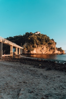 Beach surrounded by the sea and rocks covered in greenery with a bridge in brazil