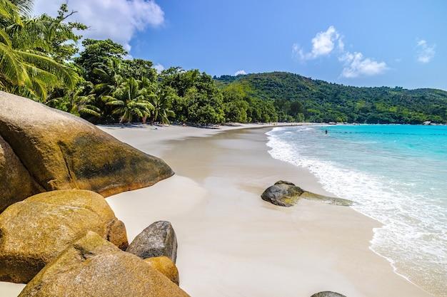 Пляж в окружении моря и зелени под солнечным светом и голубым небом на праслине на сейшельских островах