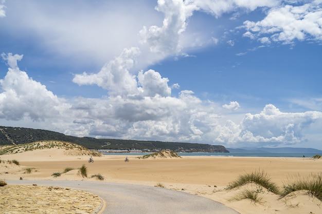 스페인 안달루시아의 흐린 하늘 아래 녹지로 덮인 바다와 언덕으로 둘러싸인 해변