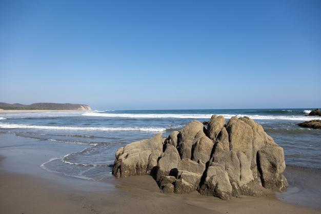 멕시코의 햇빛과 푸른 하늘 아래 바다와 바위로 둘러싸인 해변