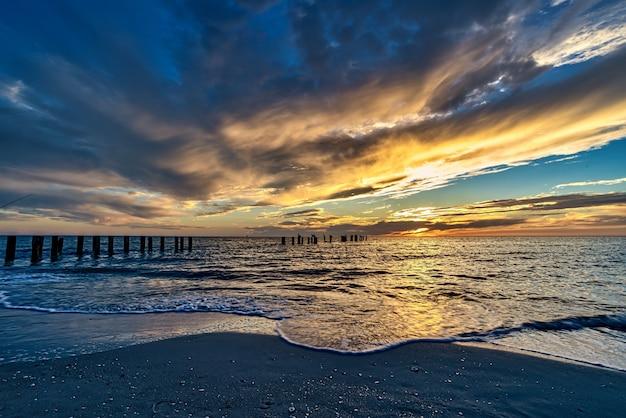 저녁 일몰 동안에 수직 나무 판자가있는 바다로 둘러싸인 해변