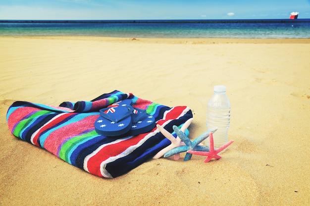 Пляжное полотенце и бутылка прохладной воды на песчаном пляже у моря