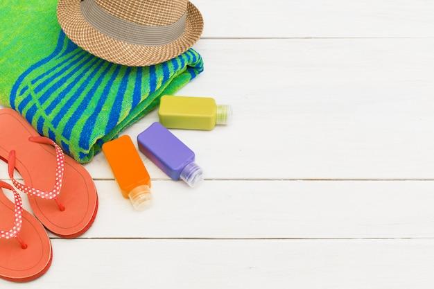Beach towel and sunscreen cream bottles on wooden wall