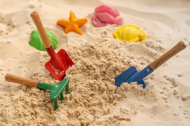 Пляжные игрушки на песке летом.