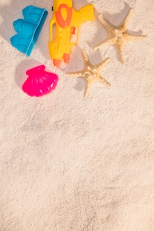 Beach toys and starfish on sand