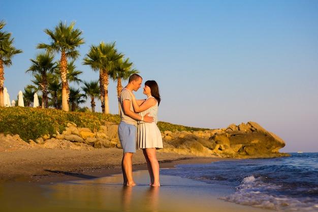 ビーチ旅行-砂浜に立っている愛のカップル