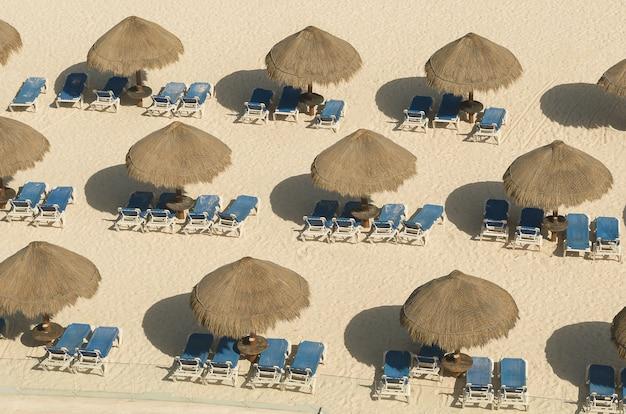 カンクンの砂の中の肘掛け椅子のビーチパラソル