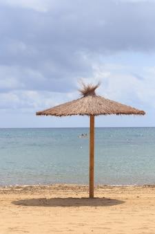 Пляжный зонт из сушеных листьев у моря.