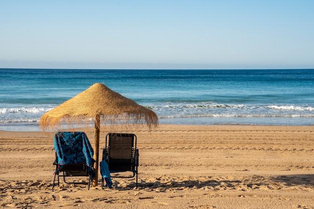 Beach umbrella with blue sky and two hammocks