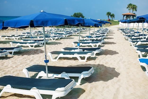 シーズンの終わりまたは始まりのビーチパラソルとサンベッド。観光の概念。