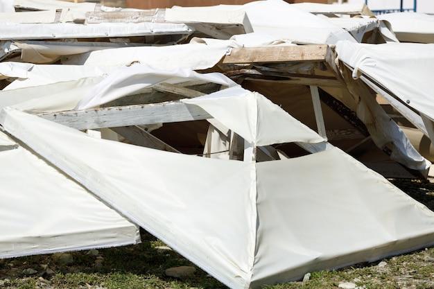 Зонтики лежат на пляже после урагана. природная катастрофа. шторм на море. фото высокого качества