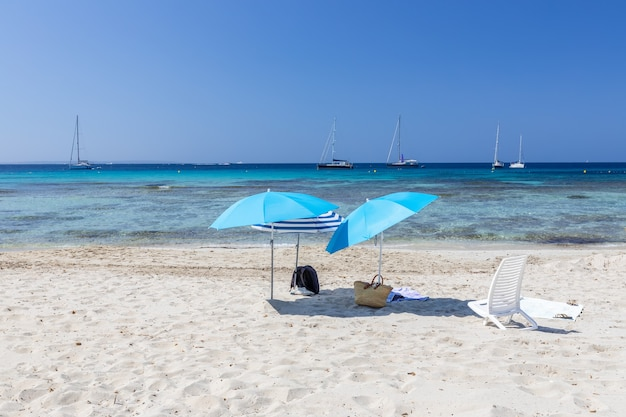 Зонтики на белом песке у бирюзового моря на пляже ses salines. остров ибица. балеарские острова, испания