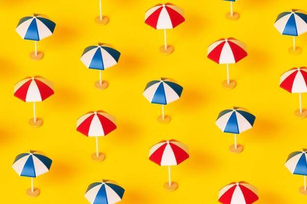 노란색 배경, 여름 휴가 개념 위에 비치 파라솔 패턴