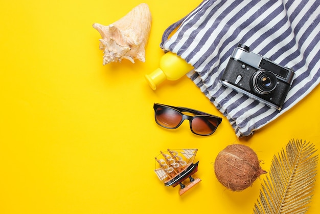 Beach vacation accessories on a yellow background. summer creative background.