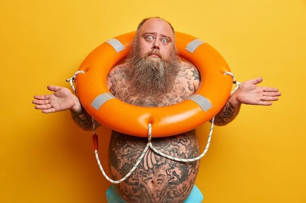 ビーチでの休暇と夏時間の概念。疑わしい混乱した太りすぎの男は肩をすくめ、ジレンマに直面し、膨らんだ救命浮輪で裸でポーズをとり、わからない、大きなおなか。ふっくら知らない救助者、命の恩人
