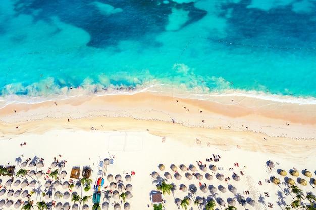 해변 휴가 및 여행 배경입니다. 짚 우산, 야자수, 보트가 있는 아름다운 대서양 열대 해변의 공중 무인 항공기. 바바로 해변, 푼타 카나, 도미니카 공화국.