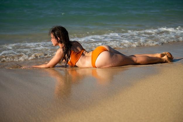 Beach vacation. beautiful woman in bikini laying on beach and enjoying view of beach ocean on summer day, hawaii.
