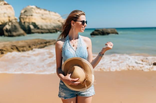 ビーチでの休暇。ビーチの上を歩く完璧な晴れた日を楽しむsunhatの美しい女性。幸せと至福。