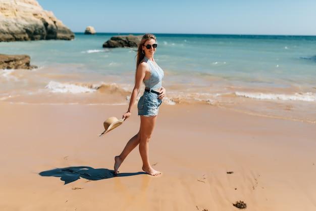 Пляжный отдых. красивая женщина в шляпе от солнца, наслаждаясь прекрасным солнечным днем, гуляя по пляжу. счастья и блаженства.