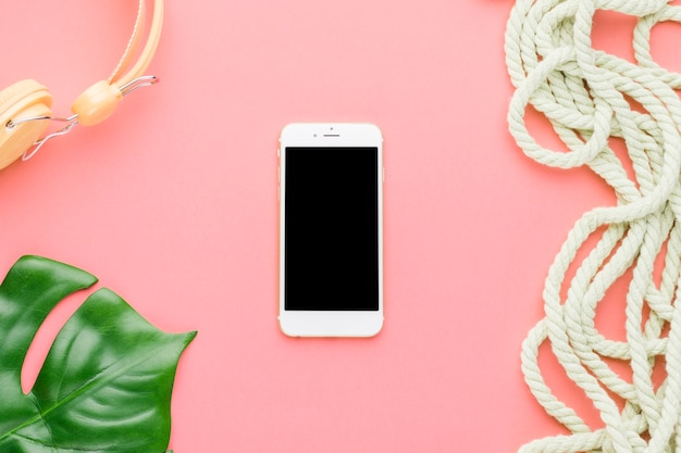 Composizione di vacanza in spiaggia con il telefono cellulare su sfondo colorato