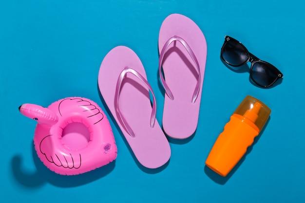 ビーチでの休暇。インフレータブルフラミンゴ、ビーチサンダル、日焼け止めボトル、ブライトブルーのサングラス