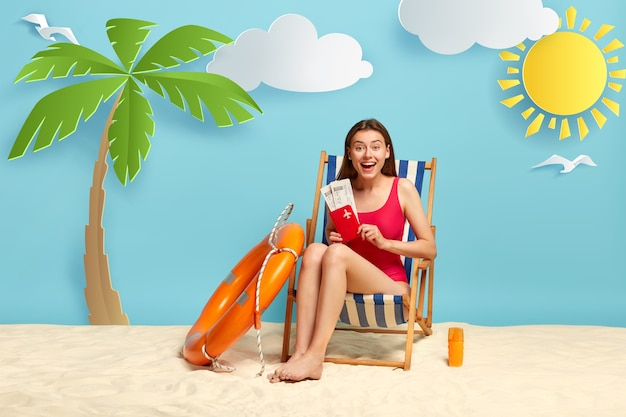 Beach vacation and relaxation concept. beautiful delighted female rejoices summer trip, holds passport with flying tickets, has fine seaside resort
