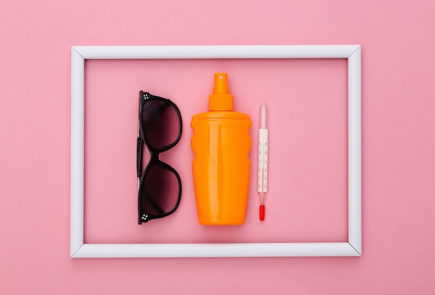 Beach vacation. summer. sunblock bottle, sunglasses and thermometer on pink with white frame