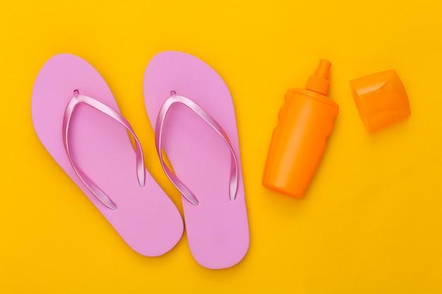 ビーチでの休暇。黄色の日焼け止めボトルとビーチサンダル