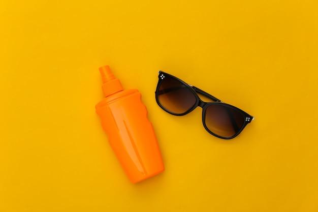 ビーチでの休暇。黄色の日焼け止めボトルとサングラス