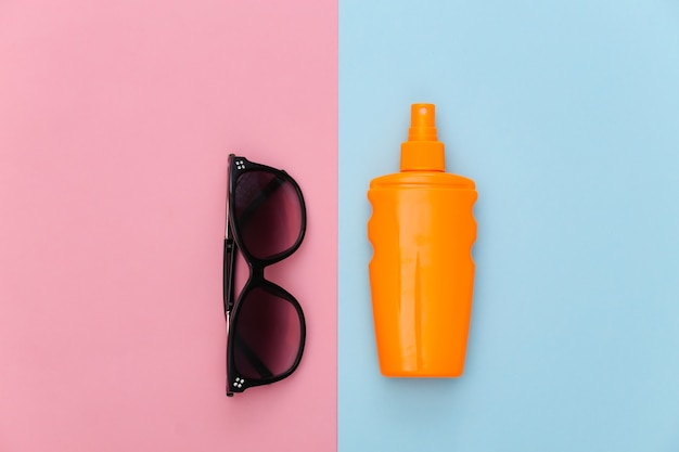 Beach vacation. sunblock bottle and sunglasses on pink blue