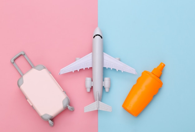 Beach vacation, travel concept. mini toy travel luggage, air plane and sunblock bottle on pink blue