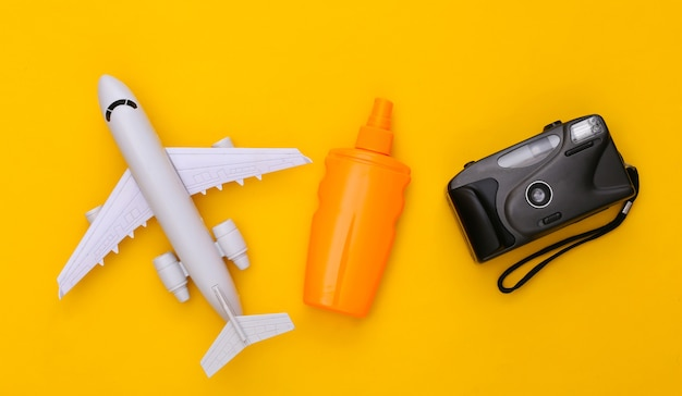 Beach vacation, travel concept. sunblock bottle, air plane and camera on yellow