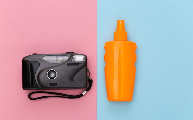 Beach vacation, travel concept. sunblock bottle and camera on pink blue