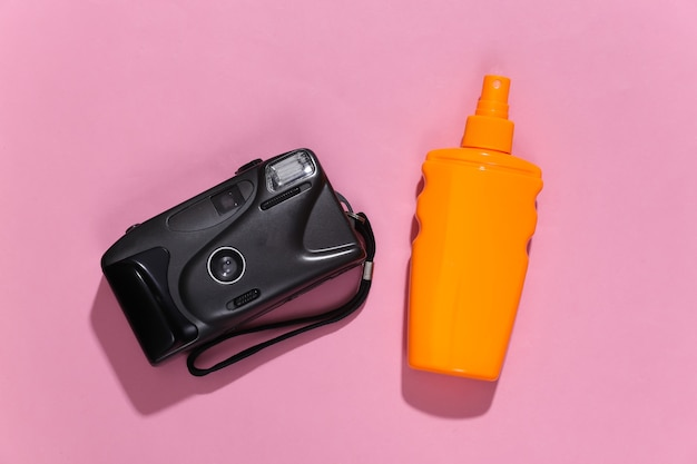 Beach vacation, travel concept. sunblock bottle and camera on pink bright sunny