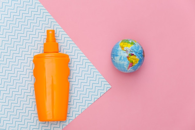 Beach vacation, travel concept. sunblock bottle and globe on pink blue