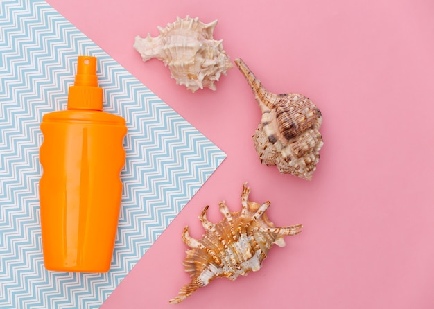 Beach vacation, travel concept. sunblock bottle and seashell on pink blue