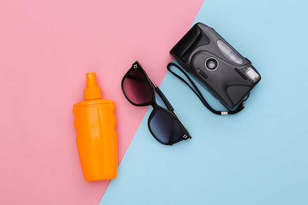 Beach vacation, travel concept. sunblock bottle, sunglasses and camera on pink blue