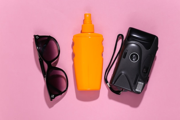 Beach vacation, travel concept. sunblock bottle, sunglasses and camera on pink bright sunny