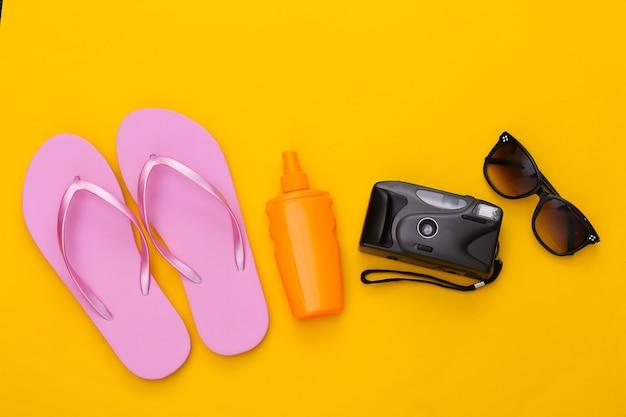 해변 휴가, 여행 개념. 선크림 병, 선글라스, 플립 플롭, 노란색 카메라
