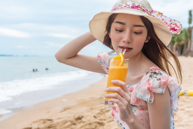 Beach vacation woman drinking orange juice having fun on the beach.