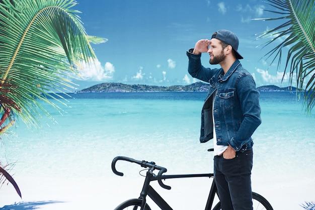 해변 휴가 기대 자전거와 함께 해변에 서 있는 세련 된 젊은이 흥분