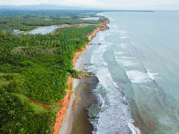 Beach view from the air with beautiful blue sea and beautiful green forest on indonesian coast
