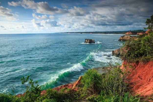 Вид на пляж с голубой морской водой и холмы с красивой зеленой травой