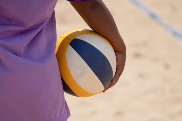 A beach volleyball athlete holding beach volleyball in hand