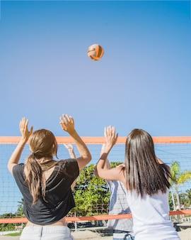 Пляжная волейбольная сцена с девушками в сети