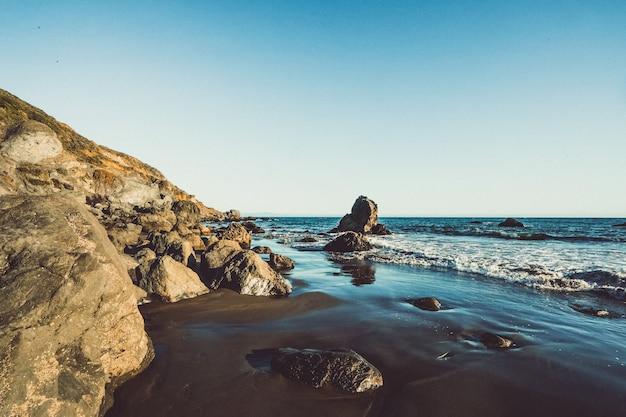 La spiaggia ondeggia colpendo la riva con le rocce un giorno soleggiato a marin, la california